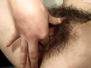 Very hairy girl plays with her bush