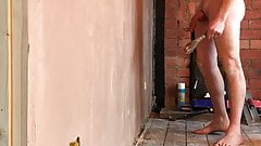 Nudist builder troweling up wall naked