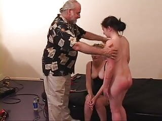 Master and mistress pull on submissive sluts nipples on the bed