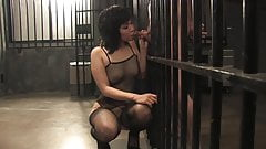 Prison harlot in net body suit give blowie between the bars
