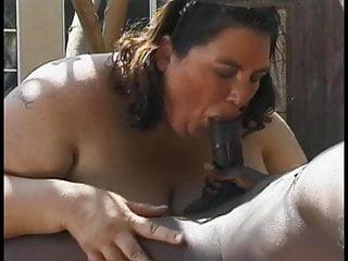 Obese brunette sucks prone black dude's big cock outdoors