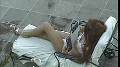 Dark nippled tranny shows off her legs and asshole on lawnchair