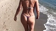 Mature Milf walks along the beach in a thong bikini