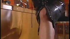 Latex-clad lesbians using a dildo
