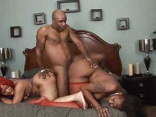 Lucky stud lays in bed and gets his cock sucked by two ebony freaks