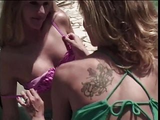 Blonde MILFs play with strap-on and anal beads by the pool