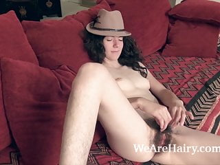 Silki Smith strips naked and sexy on her red couch