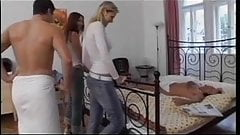 Two girls, two guys have fun together on the bed