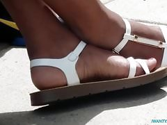 Candid ebony feet in white sandals