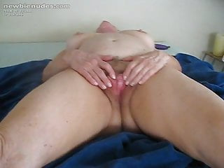 Beautiful granny lying on bed playing with her hairy pussy
