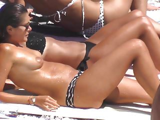 Hot topless brunette sunbathing exhibition public beach