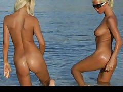 Two blond babes in string bikinis getting naked on the beach