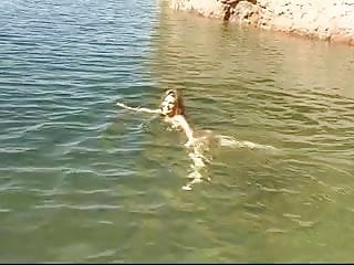 Cute young brunette strips by the water and goes skinny dipping