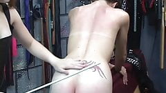 Gorgeous young brunette mistress in bdsm gear whips and spanks slave