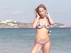 Hot blonde milf posing on public beach in string bikini